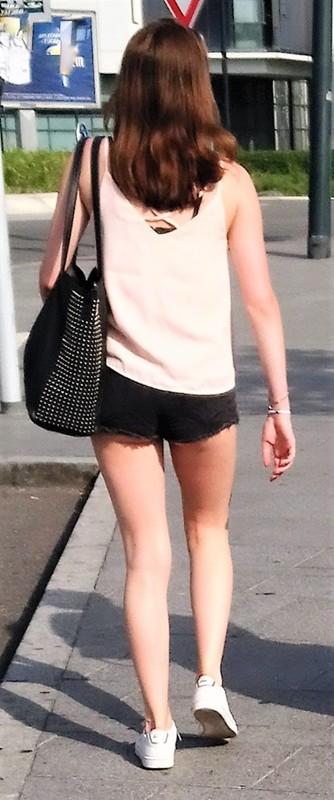 college babe walking down the street wearing black shorts