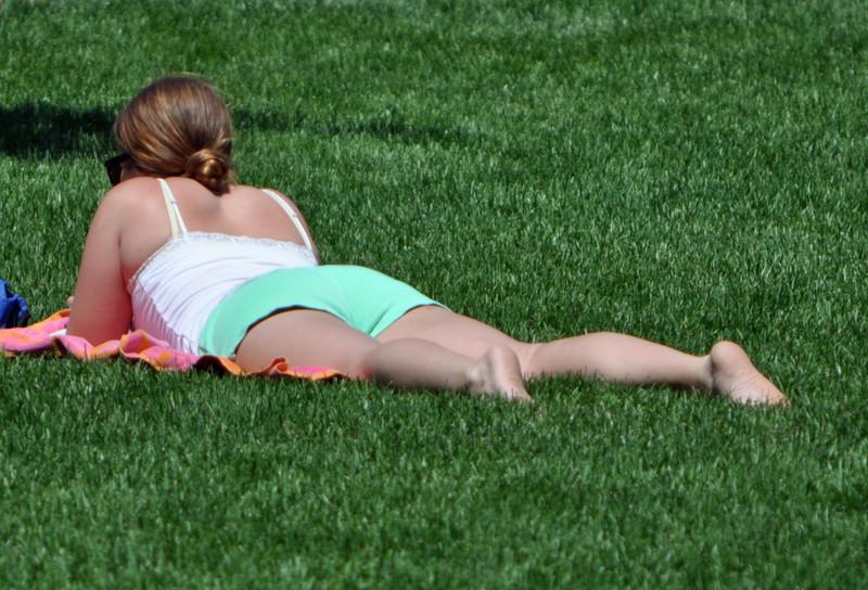 city park sunbathing girls in shorts & bikinis