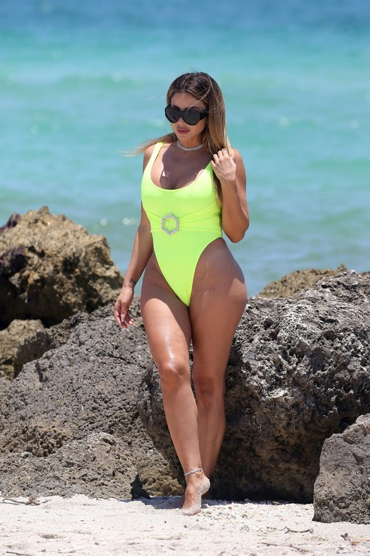 handsome milf Larsa Pippen in a neon yellow swimsuit