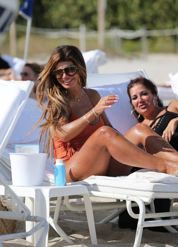 pretty milf Teresa Giudice in a orange 1 piece swimsuit
